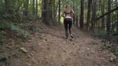 dürtmek : Young female athlete jogging in forest. Jogger doing morning physical training