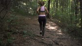 antreman : Fitness brunette girl with ponytail and sports outfit jogging in summer forest