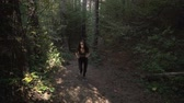 antreman : Front view, slow motion footage of fit, young woman with brown long hair trail running in forest in the morning