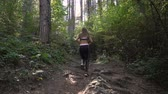 antreman : Attractive Athletic Young Woman Running Jogging In The Forest. Physical workout in the morning Stok Video