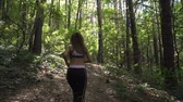 antreman : Fitness sport girl in sportswear running in forest, outdoor sport. Slow motion footage