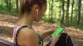 antreman : Side view of gorgeous woman with earphones choosing song from phone and preparing for morning exercise in the forest Stok Video