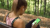antreman : Fitness girl relaxing on wooden bench in the forest after long run and listening music on earphones