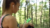 antreman : Beautiful girl in sportswear sitting on a bench in the forest, relaxing and listening music from phone Stok Video