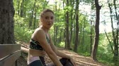 antreman : Smiling fit athletic girl sitting on a bench, confident and happy from the jogging exercise in the forest