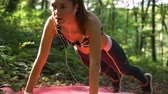 antreman : Close view of fit girl with headphones doing push ups on yoga mat in the park