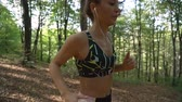 ćwiczenia : Close view of fit girl listening music and running on hard terrain in forest