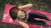 meditare : Active girl doing crunches on pink yoga mat. Abs exercises outdoors in the park Filmati Stock