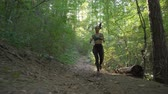 пилатес : Female jogger with earphones holding water bottle and running cross in the forest