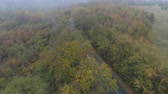 enrolamento : Aerial drone view of silver car driving alone misty road in the mountain. Forest in fall at the mountains, drone chasing car