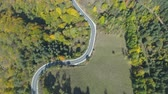 oogschaduw : Top view of scenic mountain road going trough golden forest in the mountains Stockvideo