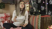 babbo natale : Happy Pregnant woman eating chocolate muffin, Christmas sweets in decorated room Filmati Stock