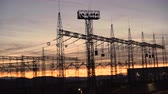 アウトライン : Distribution electric substation with power lines and transformers against beautiful sunset sky