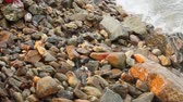 Pebble beach with small pebbles and sea surf. Waves at sunset run along rocky shore. Dostupné videozáznamy