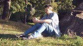 konsantre : Man is sitting on grass with phone in his hands Stok Video