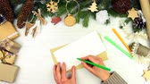 decorativo : Female woman hands writing greeting letter Merry Christmas and putting in beige envelope for winter holiday on wooden background with pine tree branches. Merry Christmas and Happy New Year concept. Stock Footage