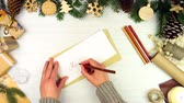 pinha : Female woman hands writing greeting letter Merry Christmas and putting in beige envelope for winter holiday on wooden background with pine tree branches. Merry Christmas and Happy New Year concept. Stock Footage