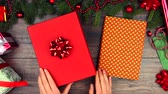 papel de embrulho : Hands of woman female adult wear fluffy winter sweater pack a New year red gift present notebook book on style wooden background with wrapping paper tinsel Christmas decorations balls bows