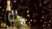birkaç : Glasses with champagne, new year golden decor, balls are on table. Clock is ticking, few minutes to midnight. Festive decorative garland, warm yellow light bulbs are blinking on background. Stok Video