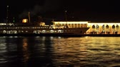 frequent : Passengers are leaving from a ferry, ship and walking on an illuminated pier, port at night Stock Footage