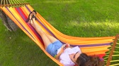 young : Slender pretty brunette laying in bright hammock and using her mobile phone, view from above. 4K shot Stock Footage