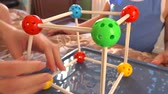 öğretici : Little boy and his mum playing with colorful plastic construction set. Molecule models. 4K close up video Stok Video