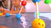 öğretici : Little boy playing with colored plastic construction set. Molecule models. 4K close up clip