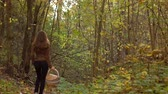 uzun yürüyüşe çıkan kimse : Girl walking in autumn forest holding a basket. 4K steadicam video