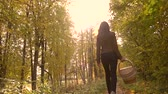 uzun yürüyüşe çıkan kimse : Slim brunette girl walking in autumn forest holding a picnic basket. 4K steadicam shot
