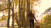 uzun yürüyüşe çıkan kimse : Brunette girl walking in autumn forest holding a basket. 4K steadicam clip Stok Video