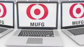 logotyp : Laptops with MUFG logo on the screen. Computer technology conceptual editorial clip, seamless loop