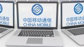 servizi informatici : Laptops with China Mobile logo on the screen. Computer technology conceptual editorial clip, seamless loop Filmati Stock