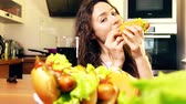 indulgence concept : Beautiful brunette young woman eating hotdog and drinking cola at home. Junk food concept. 4K video