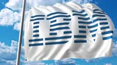 ibm : Waving flag with IBM logo against moving clouds. 4K editorial animation Stock Footage