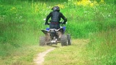 all terrain vehicle atv : Unknown man wearing protective suit riding ATV or quad on a dusty outskirts road. Slow motion shot Stock Footage