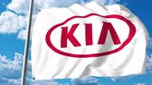 kia : Waving flag with Kia Motors logo against clouds and sky Stock Footage
