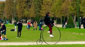 peculiar : PARIS, FRANCE - OCTOBER 7, 2017. Man riding big wheel retro bicycle on Champ de Mars near the Eiffel tower Stock Footage
