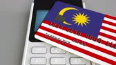 cardholder : Payment or POS terminal with credit card featuring flag of Malaysia. Malaysian retail commerce or banking system conceptual animation