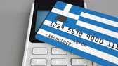 cardholder : Payment or POS terminal with credit card featuring flag of Greece. Greek retail commerce or banking system conceptual animation