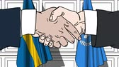 diplomat : Businessmen or politicians shake hands against flags of Sweden and United Nations. Official meeting or cooperation related editorial animation