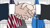 diplomat : Businessmen or politicians shake hands against flags of USA and United Nations. Official meeting or cooperation related editorial animation