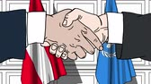 diplomat : Businessmen or politicians shake hands against flags of Austria and United Nations. Official meeting or cooperation related editorial animation