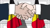 belga : Businessmen or politicians shake hands against flags of Belgium. Official meeting or cooperation related cartoon animation