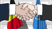 belga : Businessmen or politicians shake hands against flags of Belgium and United Nations. Official meeting or cooperation related editorial animation