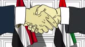 desenhado : Businessmen or politicians shake hands against flags of Egypt and UAE. Official meeting or cooperation related cartoon animation Stock Footage