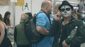 convention : POZNAN, POLAND - MAY 19, 2018. Pyrkon convention participant wearing scary faceart talking on his phone
