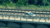 sofőr : Unrecognizable modern compact car moving along the bridge