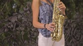 saksofon : Unrecognizable young woman playing saxophone on the street