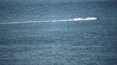 glides : Distant jet ski rider at sea, slow motion video