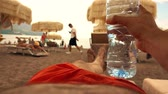 refreshment time : POV shot of a man drinking water from plastic bottle on the beach